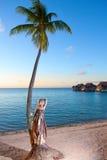 在海岸的年轻美丽的妇女和棕榈树。海热带风景 免版税图库摄影