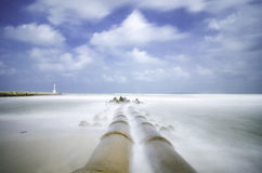 在海岸线的具体流失管道 软绵绵地击中海滩的白色波浪由于长的曝光 库存图片
