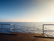 在海岸,冷的早晨,平安的沈默天的长的木码头 免版税图库摄影