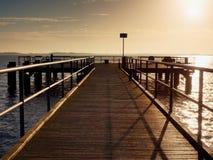 在海岸,冷的早晨,平安的沈默天的长的木码头 免版税库存照片