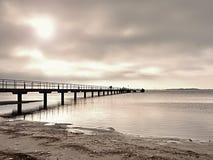 在海岸,冷的早晨,平安的沈默天的长的木码头 库存图片