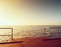在海岸,冷的早晨,平安的沈默天的长的木码头 库存照片