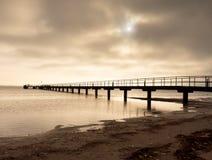 在海岸,冷的早晨,平安的沈默天的长的木码头 免版税库存图片
