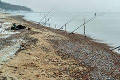 在海岸,海上,在池塘的岸安置的钓鱼竿的冬天渔的钓鱼竿 库存图片