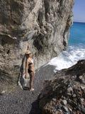 在海峭壁之间的美丽的女孩 库存照片