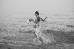 在海或海洋海滩的年轻美好的夫人奔跑在水飞溅 查出的黑色概念自由 妇女在手中运载鞋子并且走 免版税图库摄影