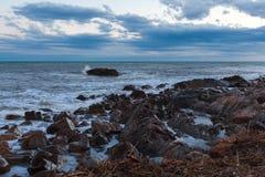 在海或海洋泡沫波浪的Sharped石头 库存照片
