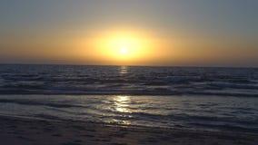 在海或海洋的惊人的日落 清楚的天空 有小波浪的风平浪静 起波纹在沙子的波浪 从的看法 股票视频