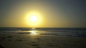 在海或海洋的惊人的美好的日落 清楚的天空 有小波浪的风平浪静 起波纹在沙子的波浪 视图 股票录像