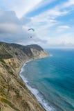 在海接近山,风景的垂直的看法的飞行的纵排滑翔伞 免版税库存照片