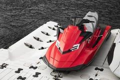 在海旁边停放的红色喷气机滑雪 免版税库存图片