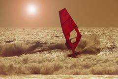 在海日落的风帆冲浪者剪影 美好的海滩海景 免版税图库摄影