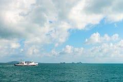 在海景的白色轮渡与天际的绿色海岛 库存图片