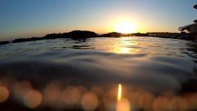 在海水的Bokeh视图,在海岸附近的波浪在日落,慢动作期间 股票视频