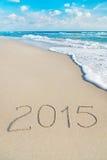 在海沙海滩的题字2015年与太阳发出光线 库存照片