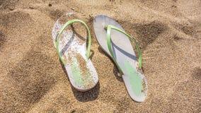 在海沙的海滩鞋子 免版税库存图片