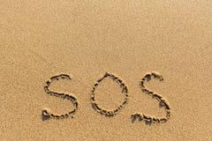 在海沙纹理-手动地写的SOS  帮助 免版税图库摄影