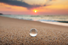 在海沙背景的水晶地球 免版税库存图片