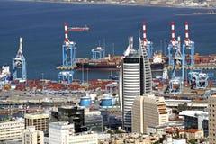 在海法航行港口起重机背景的摩天大楼  库存照片