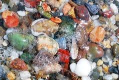 在海波浪的五颜六色的小卵石 免版税库存照片