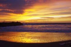 在海洋、海浪和沙子的日落 库存照片