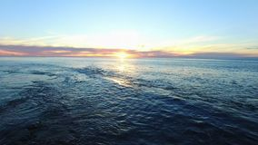 在海洋上的直升机飞行日落的 股票录像