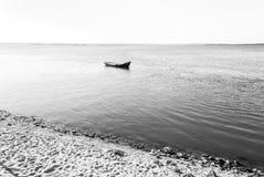 在海洋中间的偏僻的小船 免版税库存照片