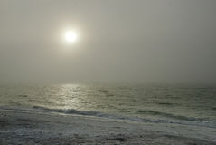 在海洋之上的有薄雾的太阳 图库摄影
