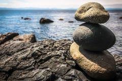 在海洋前面的被堆积的岩石形象 免版税库存照片