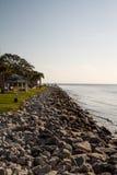在海洋和公园之间的岩石防波堤 免版税库存图片