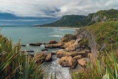 在海洋和多云天空,美好的新西兰风景的峭壁 图库摄影