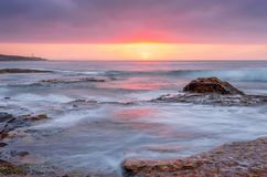 在海洋和岩石reeef的日出 库存照片