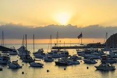 在海洋和港口的日出有小船和旗子的 免版税库存图片