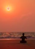 在海洋日落的瑜伽执行。 人的剪影。 免版税库存照片