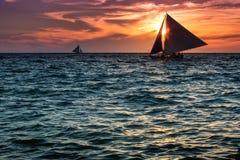 在海洋水的风船日落 库存图片