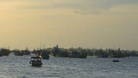 在海洋海湾的小船漂泊在风暴以后的波浪中在日落 股票视频