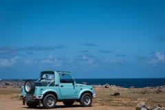 在海洋附近停放的老异乎寻常的吉普 免版税库存照片