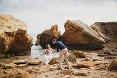 在海洋附近的室外海滩婚礼仪式,浪漫愉快的夫妇坐石头在海滩 免版税图库摄影