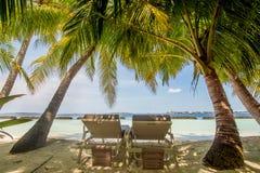 在海洋附近的美丽的热带晴朗的海滩有两sunbeds的 免版税库存图片