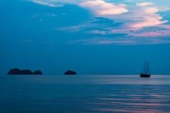 在海洋黑暗的日落天空的船 免版税库存图片