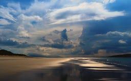 在海洋,黄沙和黄色强光的日落在大海,在蓝天白色积云 免版税图库摄影