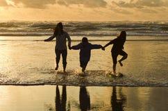 在海浪的家庭奔跑在日落 图库摄影