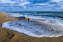 在海浪的靠岸的小船击毁 库存照片