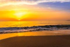 在海海浪的金黄日出日落 库存图片