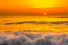 在海海浪的金黄日出日落 库存照片