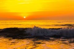 在海海浪的金黄日出日落 免版税库存图片