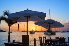 在海海滩咖啡馆或餐馆、小船、船和游艇剪影的美好的日落在水背景 免版税库存照片