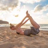 在海海滩的女子实践的瑜伽在日落 库存图片