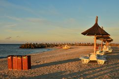 在海海滩的日出 伞,垃圾桶 免版税库存照片