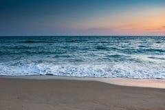在海海滩的波浪在天空蔚蓝和橙色云彩 库存图片